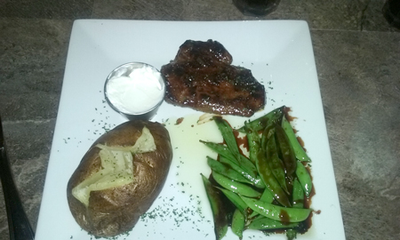 Sirloin Steak with sides of sugar snap peas and baked potato